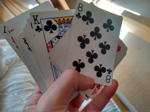 Hand holding a deck of playing cards - Oberg Law Group APC