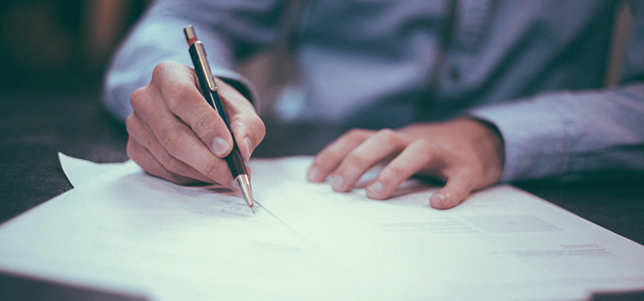 Mans hand signing contract - Oberg Law Group APC